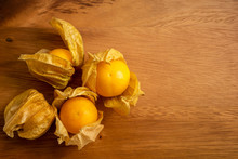 Yellow Ripe Cape Gooseberry Fruit In A Brown Wooden Background Know As Goldenberry Or Physalis, Top View Image