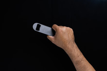 A Man Hand Holdind A Black Bottle Opener Isolated On Black Background.