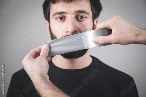 Photo Caucasian man with tape on mouth. Censorship