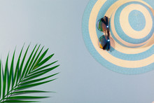 Top View On Beach Accessories On Turquoise Blue Background - Sunglasses, Blue Striped Hat And Palm Leaf. Concept Of Beach Holiday, Sea Tour, Warm Sunny Summer. Advertising Space