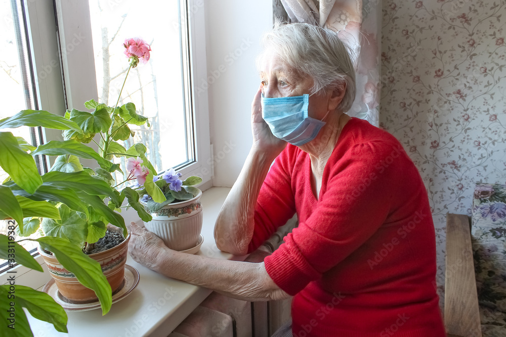 Fototapeta The Covid-19, health, safety and pandemic concept - senior old lonely woman sitting near the window
