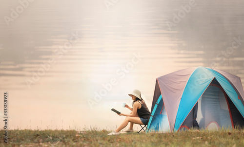 Fototapeta asian woman camping and tent outdoors near the lake. obraz