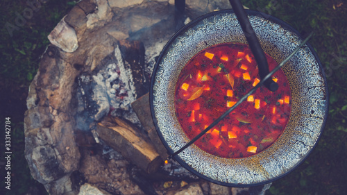Foto Cooking goulash soup in a cauldron on open fire in the woods