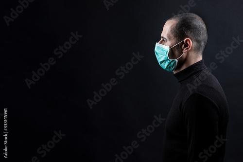 Mezzo busto laterale di un uomo rasato che  indossa una mascherina chirurgica ve Tablou Canvas