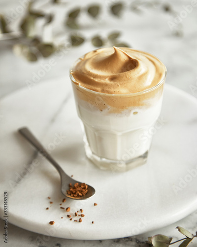 Fototapeta Dalgona coffee In a transparent glass on a marble background