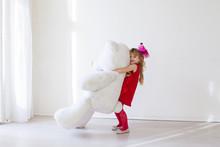 Little Girl Holds A White Teddy Bear Toy