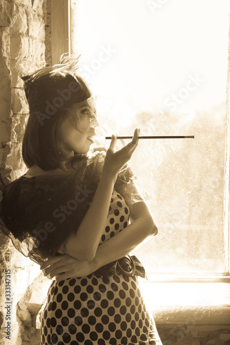 Photo Retro image of beautiful woman near window with mouthpiece