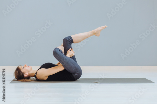 Fototapeta Relaxing back pain exercise concept. Attractive sportive woman doing pilates exercise lying on yoga mat at empty room at grey wall ackground. obraz