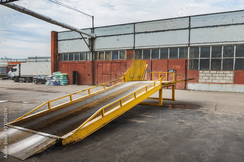 Fototapeta Metal ramp for cargo transfer from  car to  car and unloading on a warehouse