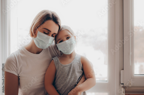 Obraz family mom and daughter in medical mask. young woman and child little girl sitting by the window in protective masks against the virus          - fototapety do salonu