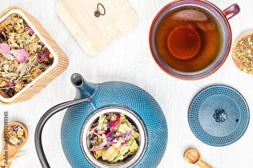 Fototapeta Traditional tea ceremony setup, teapot and teacup with herbs and dry fruits tea. Tisane detox, relaxation, healing, healthy comforting, tea time concept. Top view, flat lay obraz
