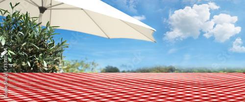 Obraz na plátně Checkered tablecloth on summer terrace