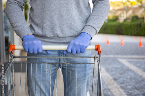 Fototapeta man in protective disposable gloves holding food trolley in store obraz