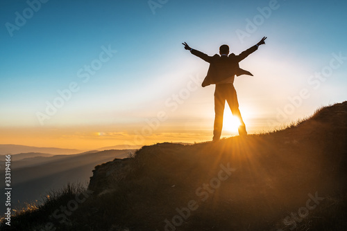 Fototapeta businessman in expensive suit, mountains and sunset obraz