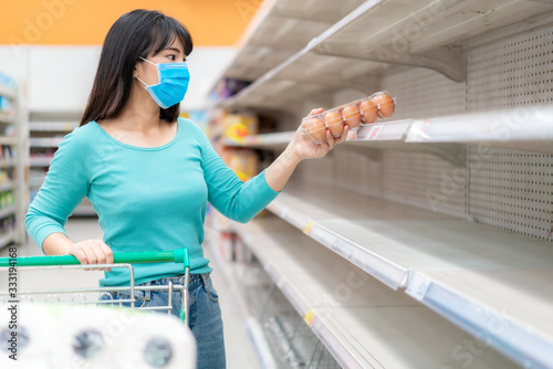 Cuadros en Lienzo Asian woman pick up last egg pack at Supermarket empty shelves amid COVID-19 coronavirus fears, shoppers panic buying and stockpiling toilet paper preparing for a pandemic