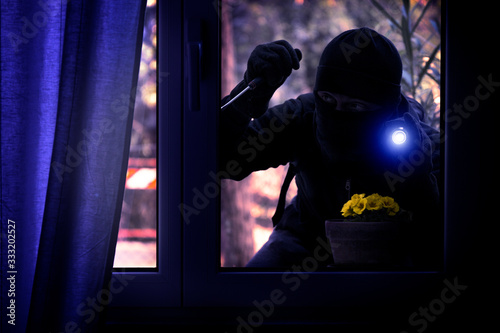 Canvastavla Hooded burglar forcing the window frame - Silhouette of thief with screwdriver a
