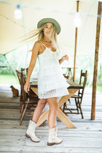 Country Girl In Stylish Boho Clothes Standing In Front Of Dinner Reception In Rustic Style, Outdoors. Beautiful Cowboy Woman With Long Blond Hair Posing In Rustic Tent For Wedding Or Dinner