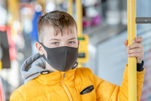 Boy Wearing Protective Mask Holding On To The Handrail In The Bus