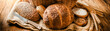 Leinwandbild Motiv Various bread with wheat on old table. Bakery food concept panorama or wide banner baker's ware photo.