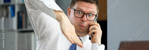 Male executive talking cellphone about bad consequences Wallpaper Mural