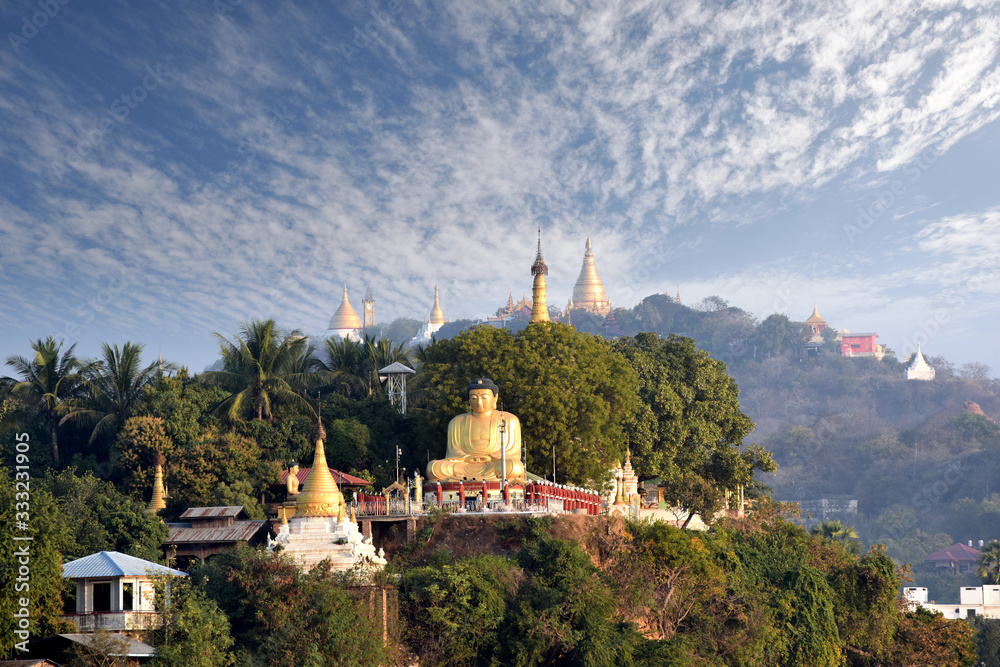 sitting buddha and golden pagodas on Sagaing hill by the Irrawaddy river, Mandalay, Myanmar (Burma)