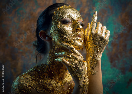 Girl with a mask on her face made of gold leaf. Gloomy studio portrait of a b...