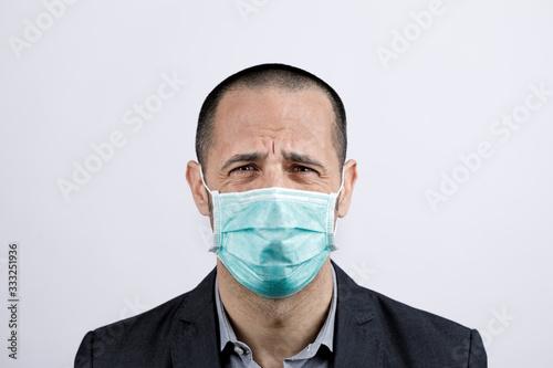Uomo in giacca e camicia con mascherina protettiva, piange disperato , isolato s Wallpaper Mural