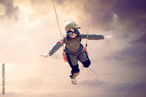 Tela happy child girl wearing an aviator outfit swinging and flying deep in a sunset