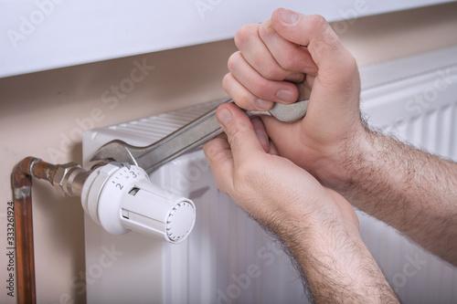 Obraz Męskie dłonie hydraulika trzymają płaski klucz którym odkręcają zawór regulujący temperaturę. - fototapety do salonu