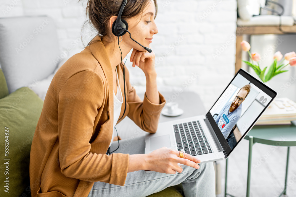Fototapeta Business woman having a video call with coworker, working online from home at cozy atmosphere. Concept of remote work from home
