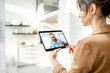 Business woman having a video call with coworker using a digital tablet, while working from home
