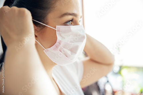 Tela Woman puts on mask that protect from bacteria and viruses