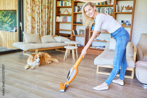 Fototapety, obrazy: Cleaning lady vacuuming the parquet in the living room