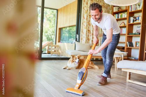 Fototapety, obrazy: Houseman vacuuming the floor