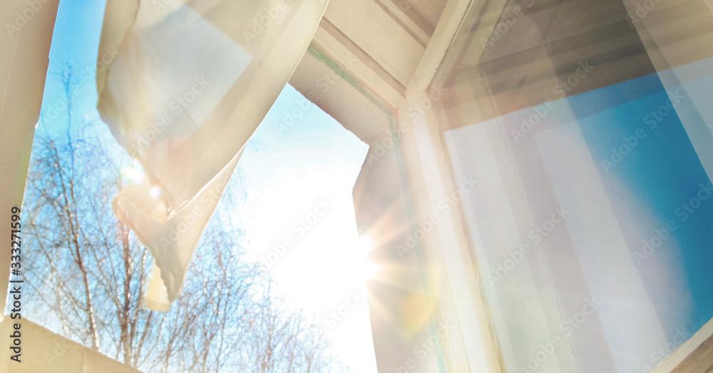 Fototapeta Window is open wind blows curtain sun shining through window
