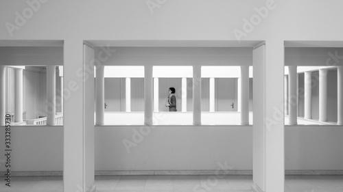 Una chica joven pasa andando entre las columnas de un edificio con paredes blanc Wallpaper Mural