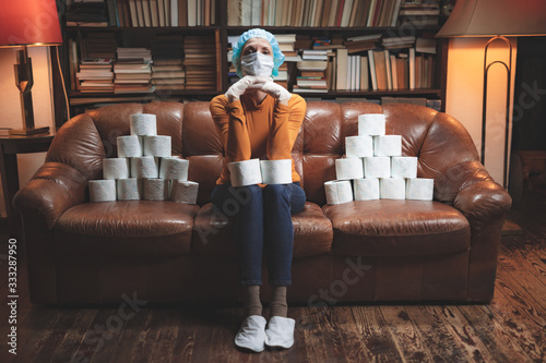 Obraz na plátně Woman with protective antiviral mask and a reserve of toilet paper waiting anxious in home isolation