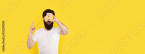 surprised bearded hipster man holding lemon slices in front of eyes, over yellow background, concept of a good idea, panoramic mock-up with space for text