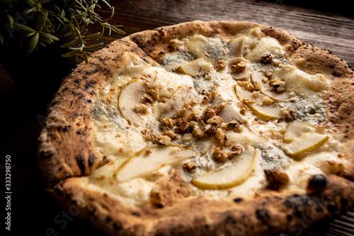 Fototapeta Pizza z gruszką, orzechami i kozim serem na drewnianym, naturalnym, brązowym stole. Obok rozmaryn w doniczce obraz
