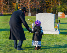 Grandfather And Granddaughter Mourn At Cemetery