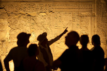 Group Of Unrecognizable Tourist Archeologists Standing In Silhouette In Front Of Ancient Egyptian Hieroglyphs