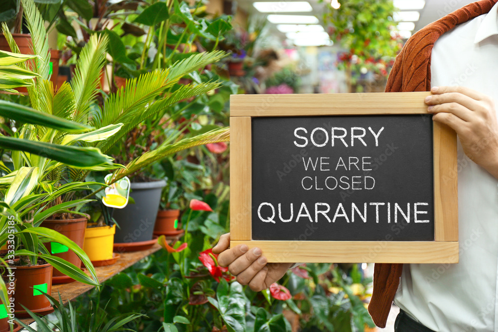 Fototapeta Business owner holding sign with text SORRY WE ARE CLOSED QUARANTINE in flower shop, closeup