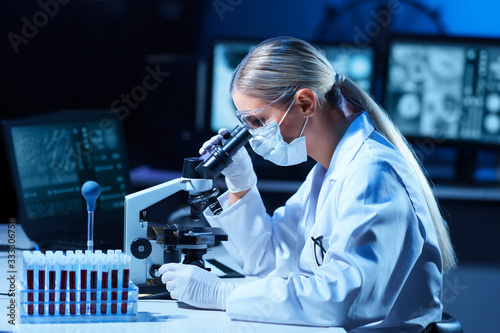 Obraz Female scientist working in modern lab. Doctor making microbiology research. Laboratory tools: microscope, test tubes, equipment. Coronavirus covid-19, bacteriology, virology, dna and health care. - fototapety do salonu