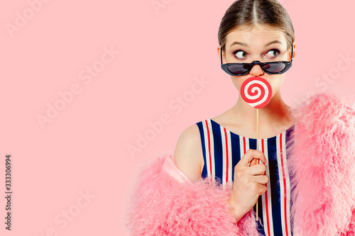 Photo a young girl averted her eyes covered her mouth with a red striped lollipop, in