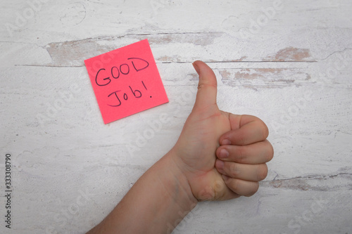 Hand giving gestureing a thumbs up with pink note with god job encouraging messa Wallpaper Mural