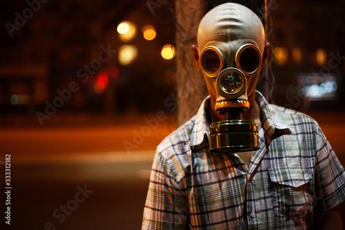 Vászonkép Man in a gas mask on night street