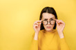 Emotion young woman keeps hands on rim of spectacles looks with omg expression gasps from shock, hears astonishing unbelievable news, dressed in sweater, isolated on yellow background with copy space