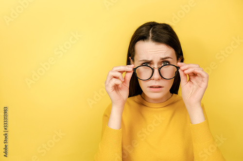 Fotografia Emotion young woman keeps hands on rim of spectacles looks with omg expression g