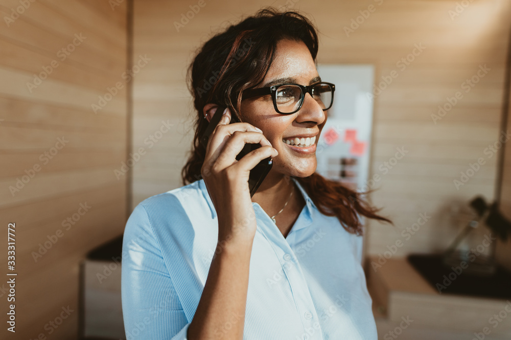 Fototapeta Woman in office talking on phone and smiling