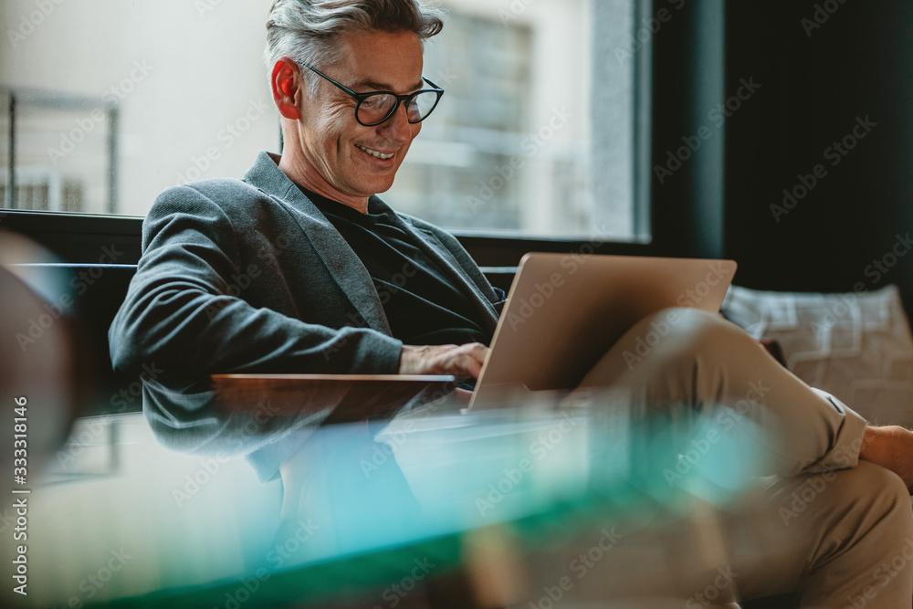 Fototapeta Business professional working on laptop in office lobby